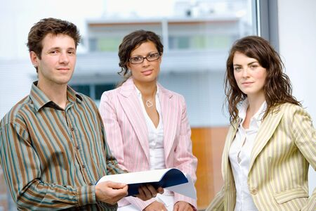 Happy young businesspeople having team meeting at office and reading documents, smiling. Stock Photo - 6550689
