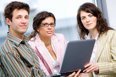 Happy businesspeople teamworking on laptop computer at office, smiling. Stock Photo - 6550671