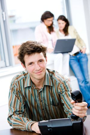Young businessman receiving phone calls at office while business people team working in background. Stock Photo - 6567195