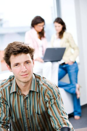 Young happy businessman looking at camera, smiling while business team working in background. Stock Photo - 6550457