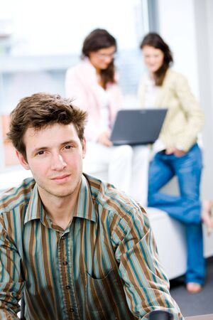 Young happy businessman looking at camera, smiling while business team working in background. Stock Photo - 6550702