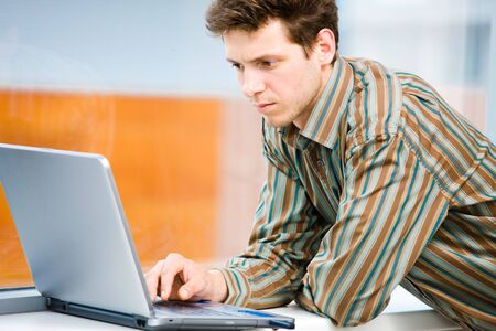 Casual looking businessman working on laptop computer in front of office window. photo