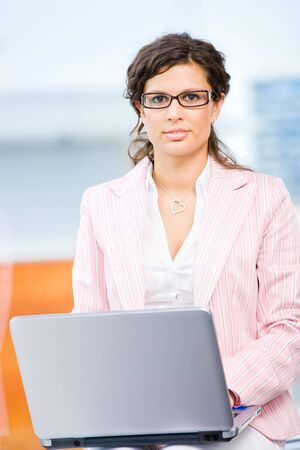 Young attractive business woman working on laptop computer in fron front of office window. Stock Photo - 6550829