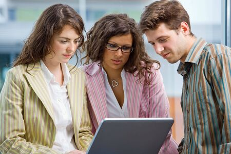 Young casual office workers having meeting at office, working in team together on laptop computer. Stock Photo - 6550633