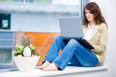 barefoot women: Young happy businesswoman sitting in office window and wokring on laptop computer, smiling.