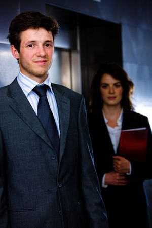 Corporate business portrait of businessman with businesswoman in background at office corridor. photo