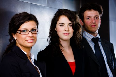 Team of happy business people standing at office corridor, looking at camera, smiling. Dark background. Stock Photo - 6550751