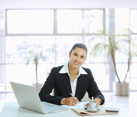 Happy businesswoman sitting at table in office lobby, writing note on paper. photo