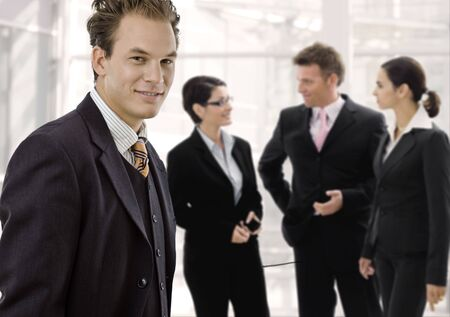 Team of 4 businesspeople standing in office lobby. Businessman in front, smiling, others talikng in the background. photo