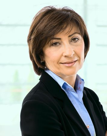 undoubting: Closeup portrait of senior businesswoman in black suit and blue shirt, smiling and looking at camera.