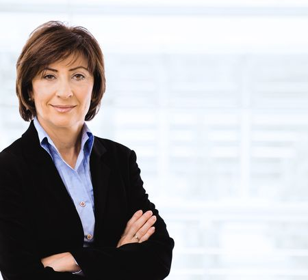 undoubting: Senior businesswoman wearing black suit and blue shirt, posing with crossed arms, smiling. Stock Photo