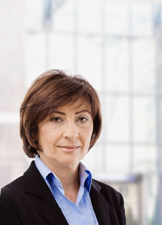 Closeup portrait of senior businesswoman in black suit and blue shirt, smiling and looking at camera, in front of windows. Stock Photo - 6550808