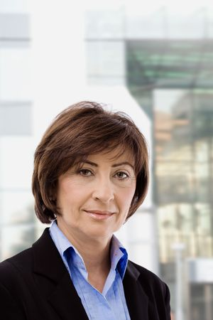 undoubting: Closeup portrait of senior businesswoman in black suit and blue shirt, smiling and looking at camera, in front of windows.