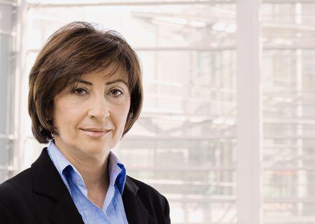 one senior adult woman: Retrato de detalle de la empresaria senior en traje negro y camisa azul, sonriente y mirando a c�mara, delante de las ventanas.