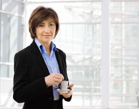 Senior businesswoman standing in front of office windows, stirring coffe, smiling. photo