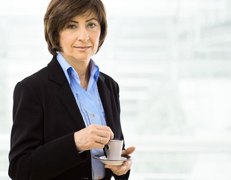 Portrait of senior businesswoman drinking coffee. photo