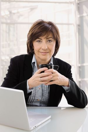 officetower: Senior businesswoman sitting at desk in front of office windows, drinking coffe, smiling.