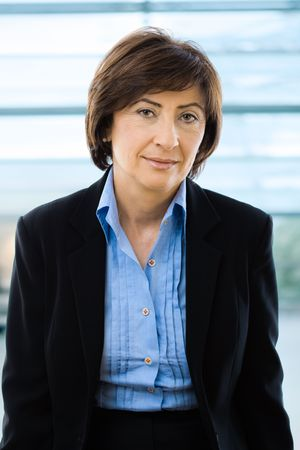 undoubting: Portrait of senior businesswoman in black suit and blue shirt, smiling and looking at camera, in front of windows.