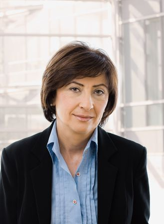 Portrait of senior businesswoman in black suit and blue shirt, smiling and looking at camera, in front of windows. photo