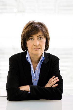 undoubting: Closeup portrait of senior businesswoman wearing grey suit, sitting at desk  arms crossed.