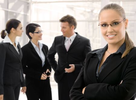 Team of 4 businesspeople gathering in office lobby. Young businesswoman wearing glasses standing arms crossed in front, smiling, others talikng in the background. photo