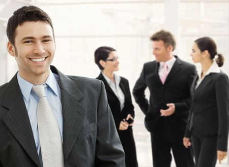 young professionals: Business team standing in office lobby. Happy businessman in front, smiling and looking at camera, others talking in the background.