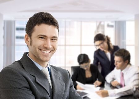 Closeup portrait of happy businessman, looking at camera, smiling. Business team working in the background, sitting at desk. photo