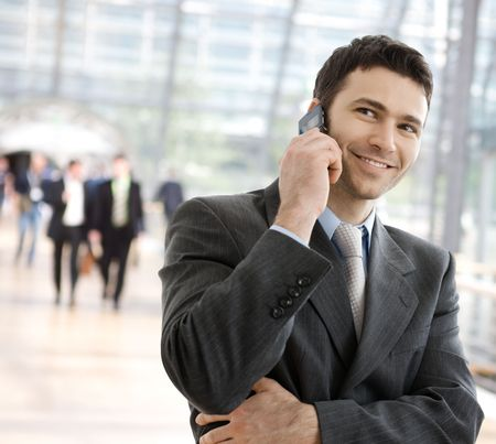 gratified: Young smiling businessman calling on phone at office.