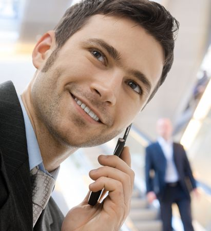 calling businessman: Young happy businessman calling on mobile phone, outdoor, smiling.