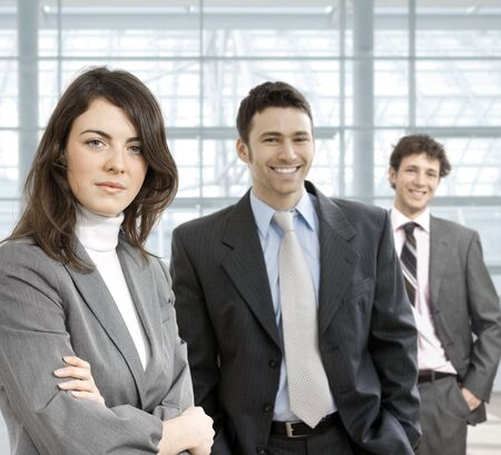 young office workers: Happy business team standing in office hallway, looking at camera, smiling.