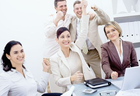 Happy business team celebrating success with arms raised, smiling. photo