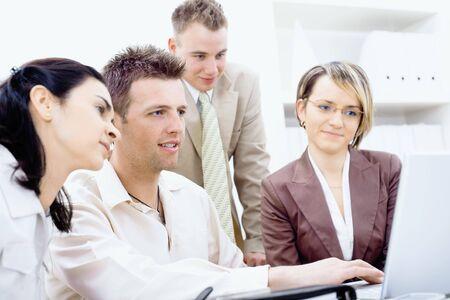 Cuatro empresarios trabajando juntos en la Oficina, utilizando equipo port�til, sonriendo. Foto de archivo - 6566742