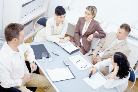 Five businesspeople sitting around table in office and having a meeting. Discussing business plans and writing notes on paper.