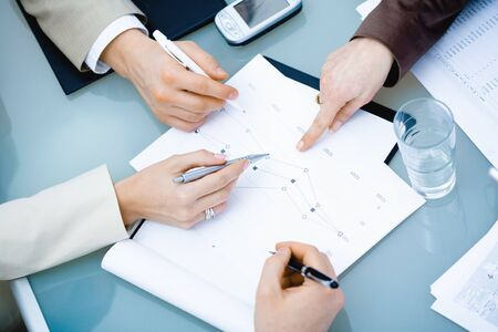 teamworking: Close-up of hands of teamworking businesspeople on meeting at office.