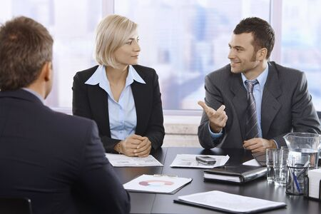 co work: Professionals discussing work sitting in meeting room. Stock Photo