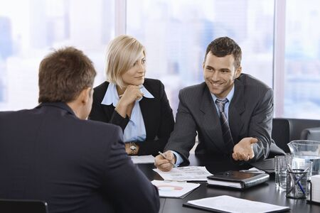 Smiling businessman discussing document at meeting with coworkers. photo