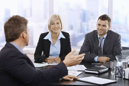 boardroom meeting:  Business meeting in skyscraper office with smiling mid-adult professionals.
