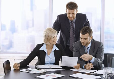 reviewing documents: Businesspeople reviewing documents together in office. Stock Photo