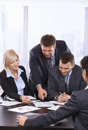 revisando documentos: Personas de negocios ocupado trabajando juntos, hablando en la reuni�n de la Oficina. Foto de archivo