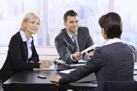 handing over: Businesspeople smiling at meeting, businessman handing over document sitting at table. Stock Photo