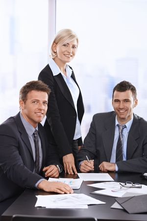buen trato: Retrato de sonrientes empresarios en reuni�n de la mesa en el cargo. Foto de archivo