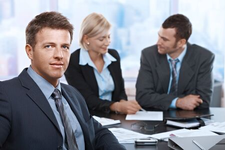 Portrait of businessman looking at camera sitting at meeting room with coworkers. photo