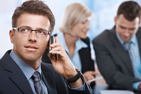 Concentrating businessman on call, coworkers talkling in background. photo