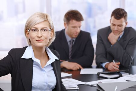 reviewing documents: Portrait of smiling businesswoman in office with coworkers reviewing documents in background.