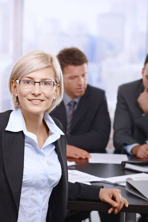 Portrait of smiling businesswoman in office with coworkers reviewing documents in background. photo