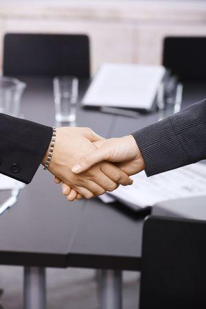 Closeup of hands. Businesswomen shaking hands over table, in office meeting room. photo