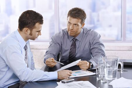 reviewing: Businessmen discussing business report sitting at meeting table in office. Stock Photo