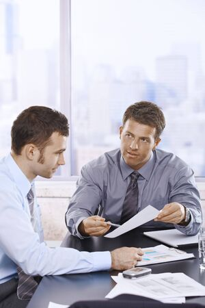 severity: Businessmen discussing business report sitting at meeting table in office. Stock Photo