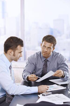 informe comercial: Empresarios de discutir el informe de negocio sentado en reuni�n de la mesa en el cargo.