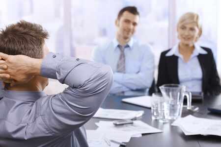 boardroom meeting: Businesspeople sitting in meeting room, smiling at executive in focus. Stock Photo